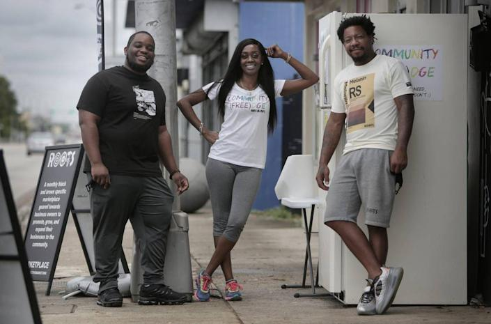 Isaiah Thomas, left, Sherina Jones and Danny Agnew by the refrigerator they placed in front of the Roots Collective to provide free food to locals.