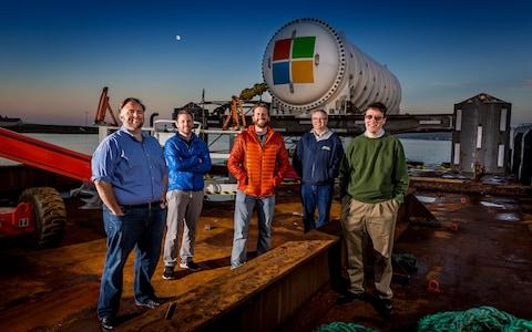Microsoft's Project Natick team gathers on a barge tied up to a dock in Scotland's Orkney Islands in preparation to deploy the Northern Isles datacenter on the seafloor. Pictured from left to right are Mike Shepperd, senior R&D engineer, Sam Ogden, senior software engineer, Spencer Fowers, senior member of technical staff, Eric Peterson, researcher, and Ben Cutler, project manager. - Credit: Microsoft