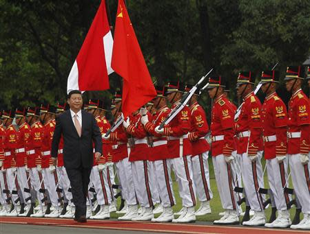 China's President Xi walks during a welcoming ceremony at the Presidential Palace in Jakarta