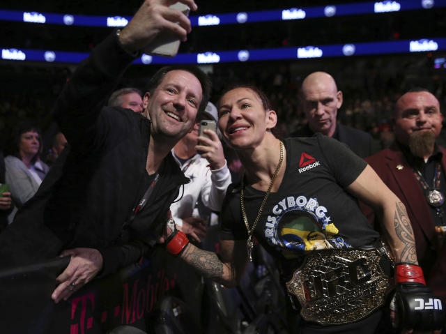 "Women's featherweight champion Cris ""Cyborg"" Justino, of Brazil, poses for a photo with a fan after defeating Yana Kunitskaya, of Russia, in a mixed martial arts bout at UFC 222 on Saturday, March 3, 2018, in Las Vegas. (Steve Marcus/Las Vegas Sun via AP)"