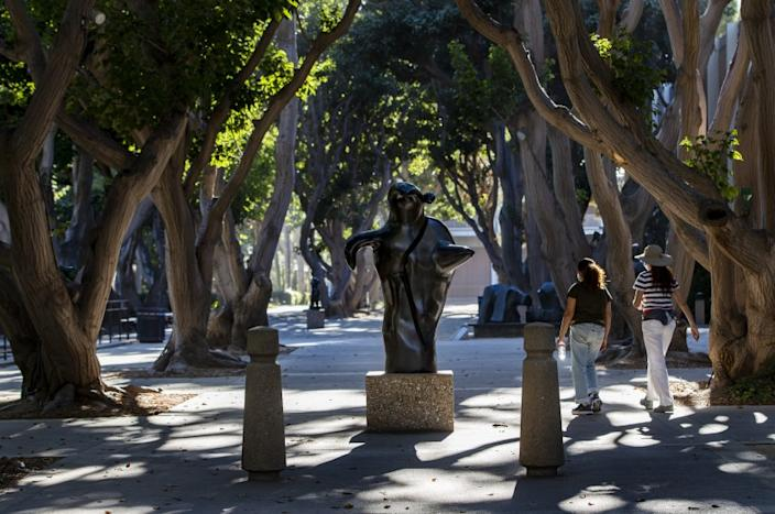 """WESTWOOD, CA - AUGUST 8, 2020: Visitors pass by Joan Miro's """"Ubu"""" in the Franklin D. Murphy Sculpture Garden at UCLA in Westwood, CA. (Gina Ferazzi / Los Angeles Times)"""
