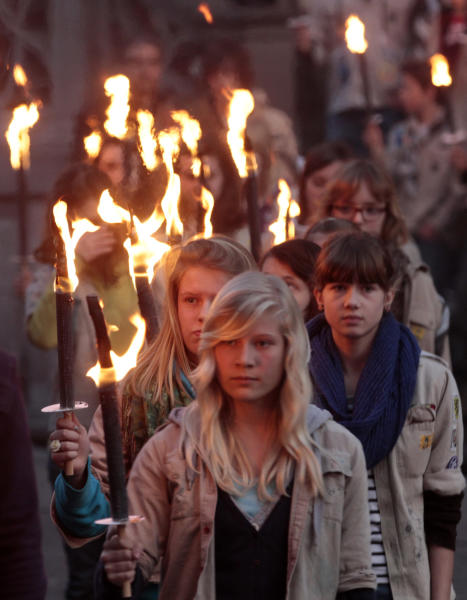 members of a local scouts group hold torches and attend a vigil in between the town hall and the Saint Peters church in Leuven, Belgium, Wednesday, March 21, 2012. Mourners attended a vigil for victims of last week's bus crash in a Swiss tunnel that killed 22 children and six adults. (AP Photo/Yves Logghe)