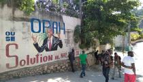 People walk past a wall with a mural depicting Haiti's President Jovenel Moise, after he was shot dead by unidentified attackers in his private residence, in Port-au-Prince
