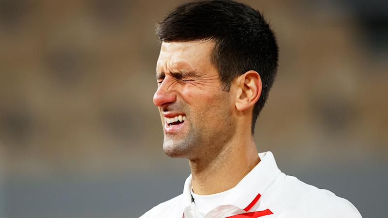 Pictured here, Novak Djokovic grimaces in pain during his French Open quarter-final.