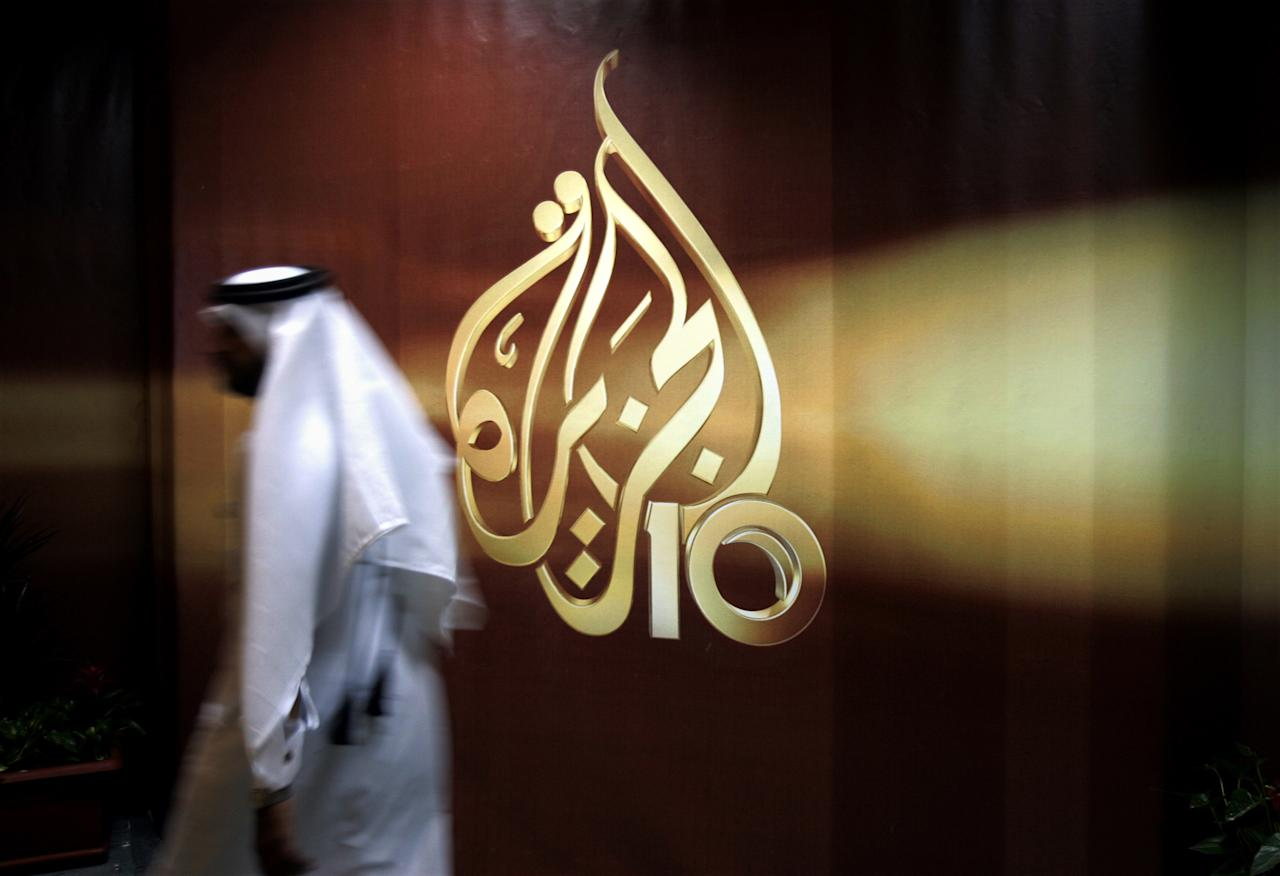 <p> FILE -- In this Nov. 1, 2006 file photo, a Qatari employee of Al Jazeera Arabic language TV news channel walks past the logo of Al Jazeera in Doha, Qatar. Hackers allegedly broke into the website of Qatar's state-run news agency and published a fake story quoting the ruling emir, authorities there said Wednesday, May 24, 2017, as Saudi Arabia and the United Arab Emirates responded by blocking Qatari media, including broadcaster Al-Jazeera. (AP Photo/Kamran Jebreili, File) </p>