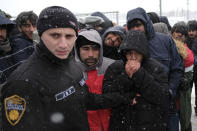 A policeman stands by migrants as they wait to be relocated during a snowfall at the Lipa camp northwestern Bosnia, near the border with Croatia, Saturday, Dec. 26, 2020. Hundreds of migrants are stranded in a burnt-out squalid camp in Bosnia as heavy snow fell in the country and temperatures dropped during a winter spell of bad weather after fire earlier this week destroyed much of the camp near the town of Bihac that already was harshly criticized by international officials and aid groups as inadequate for housing refugees and migrants.(AP Photo/Kemal Softic)