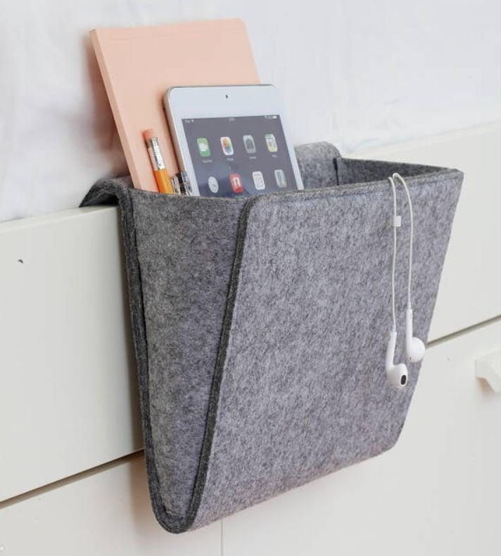 <p>This <span>Bedside Essentials Pocket<br> </span> ($15) is great for someone who has a ton of gadgets and is missing a nightstand.</p>