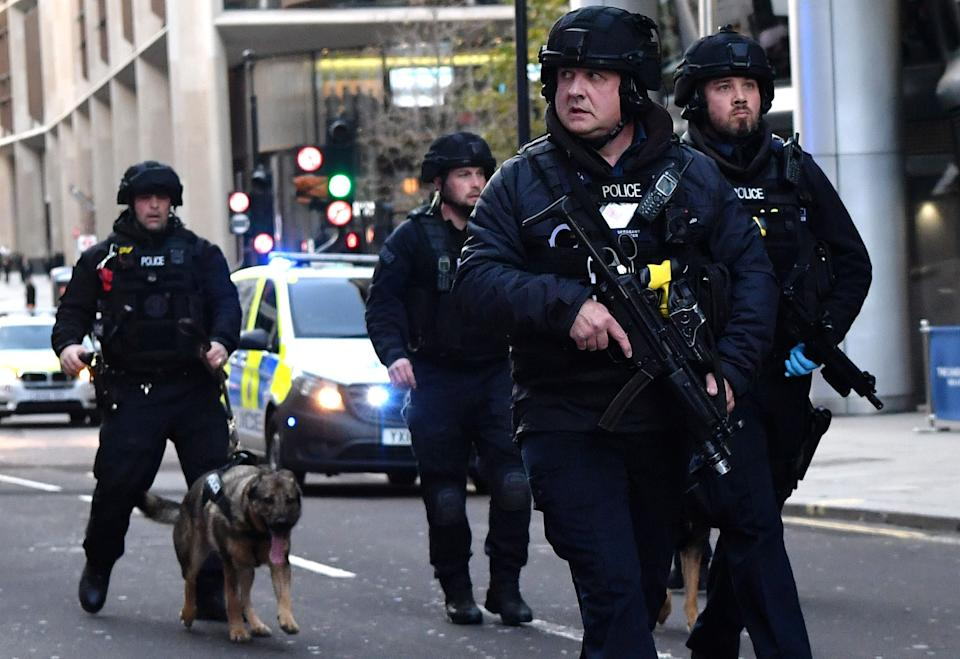 <p>Armed police with dogs patrolling along Cannon Street on November 29, 2019,  after reports of shots being fired on London Bridge</p>AFP via Getty Images