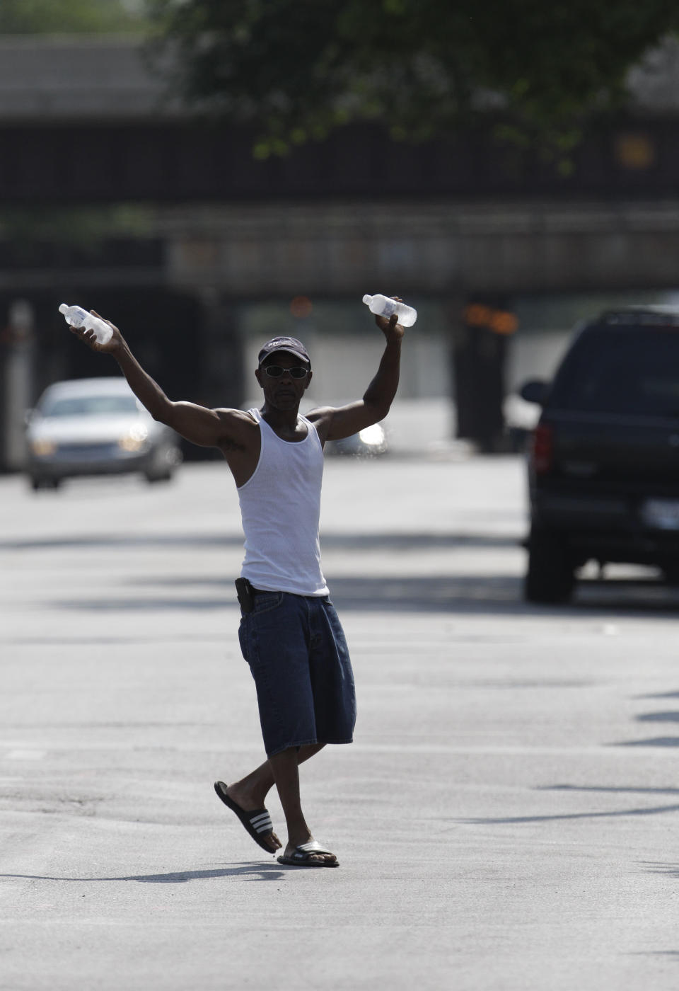 An entrepreneur hawks bottled water to passing motorists along Emmett Till Dr., in Chicago during a continuing heat wave Friday, July 6, 2012. Temperatures in the city are expected to be over 100 degrees for a third straight day. (AP Photo/M. Spencer Green)
