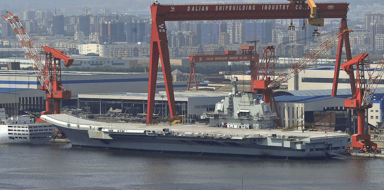 In this photo taken on Aug. 6, 2011, a Chinese aircraft carrier, which had been under refurbishment, is docked at Dalian port in in northeast Liaoning province. China's first aircraft carrier started sea trials Wednesday, Aug. 10, 2011, a step that will likely boost concerns about the country's naval ambitions amid sea territorial disputes. (AP Photo/Color China Photo) CHINA OUT