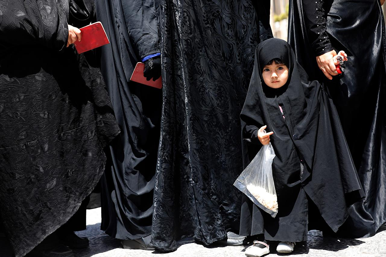 <p>A veiled little Iranian girl stands in a line with her mother among women queing to vote in the Iranian presidential elections at the polling station in the Abdol Azim shrine, in the city of Shahre-Ray, 12 km south of Tehran, Iran, May 19, 2017. Out of the candidates, the race is tightest between frontrunners Iranian current president Hassan Rouhani and conservative presidential candidate Ebrahim Raisi. (Photo: Abedin Taherkenareh/EPA) </p>
