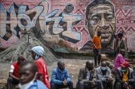 """Local residents sit next to a mural painted in June 2020 showing George Floyd with the Swahili word """"Haki"""" or """"Justice"""" in the Kibera low-income neighborhood of Nairobi, Kenya, Wednesday, April 21, 2021. After three weeks of testimony, the trial of the former police officer charged with killing George Floyd ended swiftly: barely over a day of jury deliberations, then just minutes for the verdicts to be read — guilty, guilty and guilty — and Derek Chauvin was handcuffed and taken away to prison. The guilty verdict in the George Floyd trial was not just America's victory. It signaled hope for those seeking racial justice and fighting police brutality across the Atlantic. (AP Photo/Brian Inganga)"""