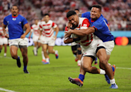 Determined to score. Determined to stop a score. Two sides of the game are revealed in this close up shot by Mike Hewitt (Getty Images). Japan's Timothy Lafaele goes on to score his side's first try in a 38 - 19 win, but it's a close run thing as Alapati Leiua of Samoa hangs on for dear life.