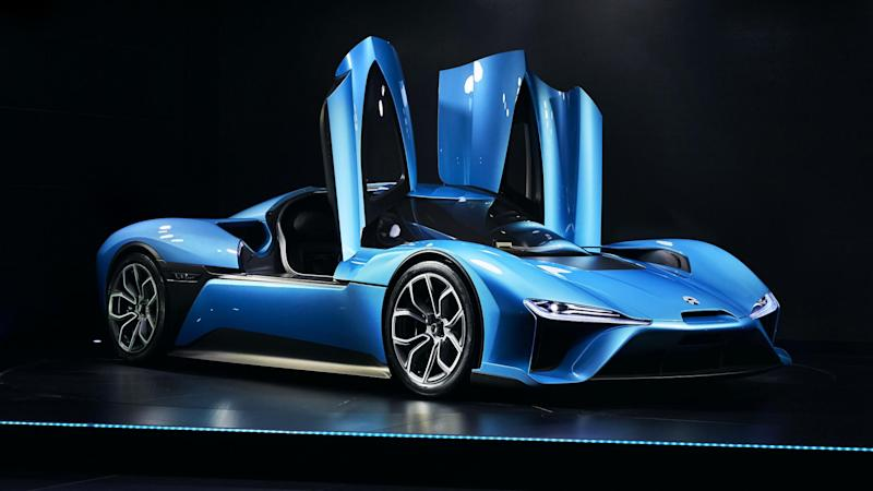 Blue sports car with doors opening upward.