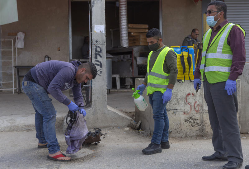 In this Tuesday, April 7, 2020 photo, a paramedic from the Palestinian Ministry of Health disinfects car parts carried by a Palestinian laborer, to help contain the coronavirus, as he exits an Israeli army checkpoint after returning from work in Israel, near the West Bank village of Nilin, west of Ramallah. The virus outbreak poses a major dilemma for tens of thousands of Palestinian laborers working inside Israel who can no longer freely travel back and forth. (AP Photo/Nasser Nasser)