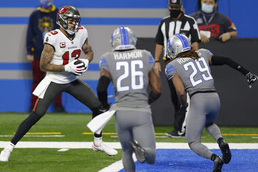 Tampa Bay Buccaneers wide receiver Mike Evans (13) prepares to step into the end zone for a touchdown as Detroit Lions cornerback Darryl Roberts (29) and strong safety Duron Harmon (26) defend during the second half of an NFL football game, Saturday, Dec. 26, 2020, in Detroit. (AP Photo/Al Goldis)