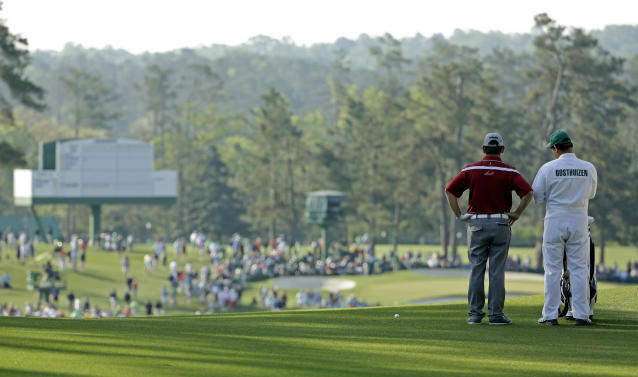 Louis Oosthuizen, of South Africa, and his caddie Wynand Stander look over the second fairway during the second round of the Masters golf tournament Friday, April 11, 2014, in Augusta, Ga. (AP Photo/David J. Phillip)