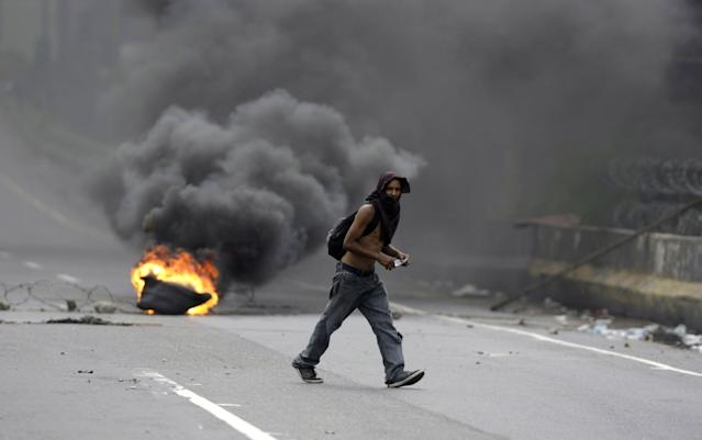 <p>A demonstrators walks by to a burning barricaded on a highway during a national sit-in against President Nicolas Maduro, in Caracas, Venezuela, Monday, May 15, 2017. (AP Photo/Fernando Llano) </p>