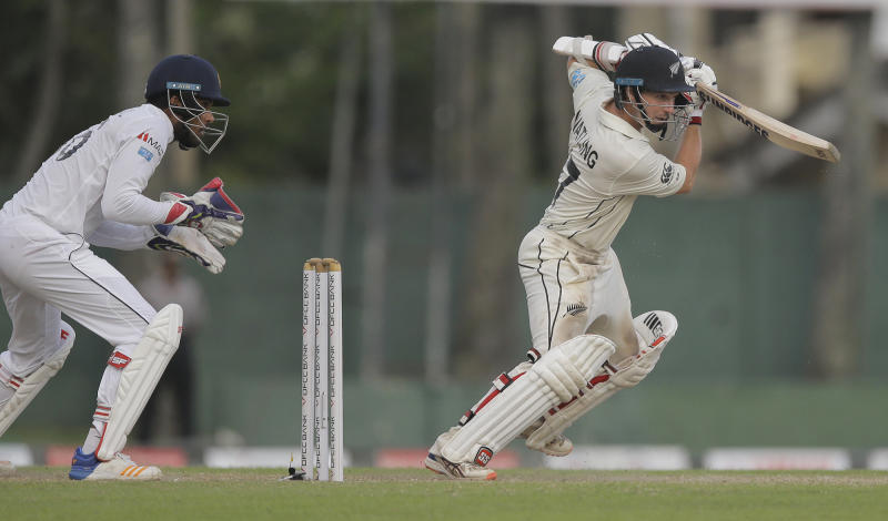 New Zealand's BJ Watling plays a shot as Sri Lanka's Lahiru Thirimanne watches during day four of the second test cricket match between Sri Lanka and New Zealand in Colombo, Sri Lanka, Sunday, Aug. 25, 2019. (AP Photo/Eranga Jayawardena)