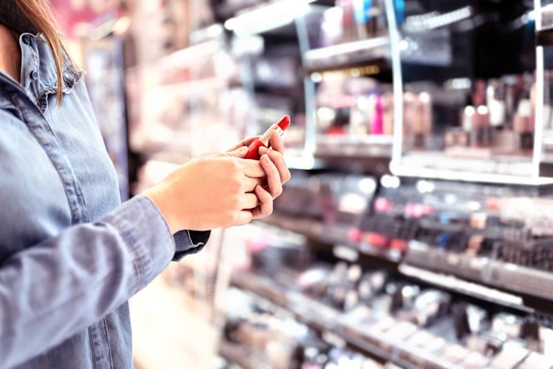 Woman buying make up at cosmetics section in store. Customer shopping beauty products. Choosing red lipstick from shelf and selection. Using tester. Makeup business concept. Supermarket or drugstore.