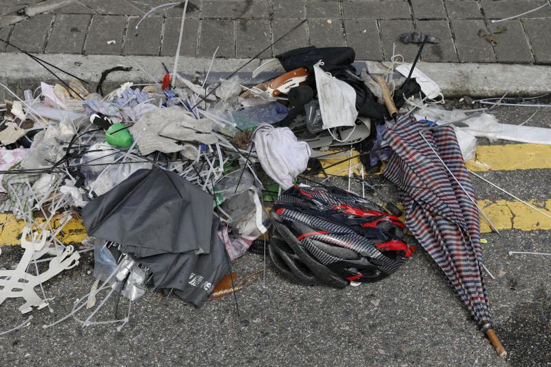 In this Friday, June 14, 2019, photo, broken umbrellas left in the aftermath of Wednesday's violent protest against proposed amendments to an extradition law are seen in Hong Kong. Umbrellas became a symbol of protest in Hong Kong in 2014 after demonstrators used them to shield themselves from both police pepper spray and a hot sun. Five years later, umbrellas were out in force again on Wednesday as thousands of protesters faced off with police outside the legislature. (AP Photo/Vincent Yu)