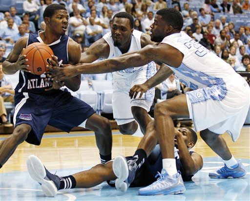 North Carolina's P.J. Hairston and Reggie Bullock (35) guard Florida Atlantic's Cavon Baker as Jordan McCoy falls to the floor during the first half of an NCAA college basketball game in Chapel Hill, N.C., Sunday, Nov. 11, 2012. (AP Photo/Gerry Broome)