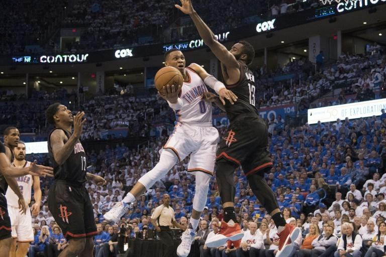 Russell Westbrook of the Oklahoma City Thunder drives around James Harden of the Houston Rockets during Game Three in the  Western Conference Quarterfinals