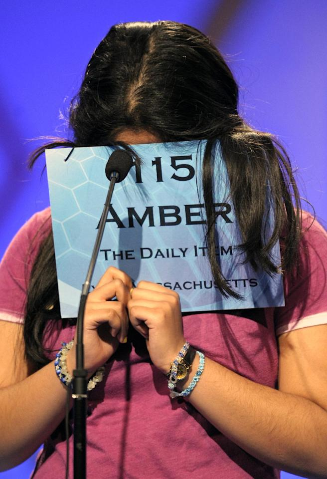 "Amber Born, 14 of Marblehead, Mass., covers her face while spelling ""malacophilous"" during the semifinal round of the Scripps National Spelling Bee in Oxon Hill, Md., Thursday, May 30, 2013. (AP Photo/Cliff Owen)"