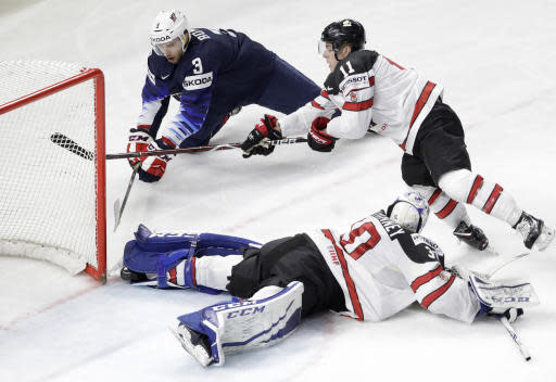 Nick Bonino of the United States, above left, challenges for the puck with Canada's Jean-Gabriel Pageau during the Ice Hockey World Championships bronze medal match between Canada and the United States at the Royal arena in Copenhagen, Denmark, Sunday, May 20, 2018. (AP Photo/Petr David Josek)