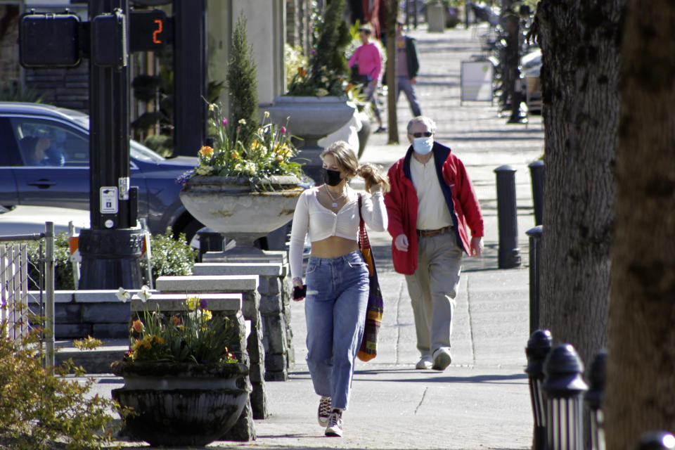Residents wearing masks walk in downtown Lake Oswego, Ore., on Sunday, April 11, 2021. Tens of thousands of Oregon residents are angry about a proposal to make permanent an emergency rule that requires masks and social distancing in the state's businesses and schools to prevent the spread of COVID-19. Opponents worry about government overreach and fear that state officials won't remove the mask requirements for businesses even after threat of the virus has receded if the emergency rule becomes permanent. (AP Photo/Gillian Flaccus)