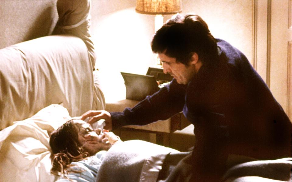 Jason Miller attends to a possessed Linda Blair in <em>The Exorcist.</em> (Photo: Warner Bros./Courtesy of the Everett Collection)