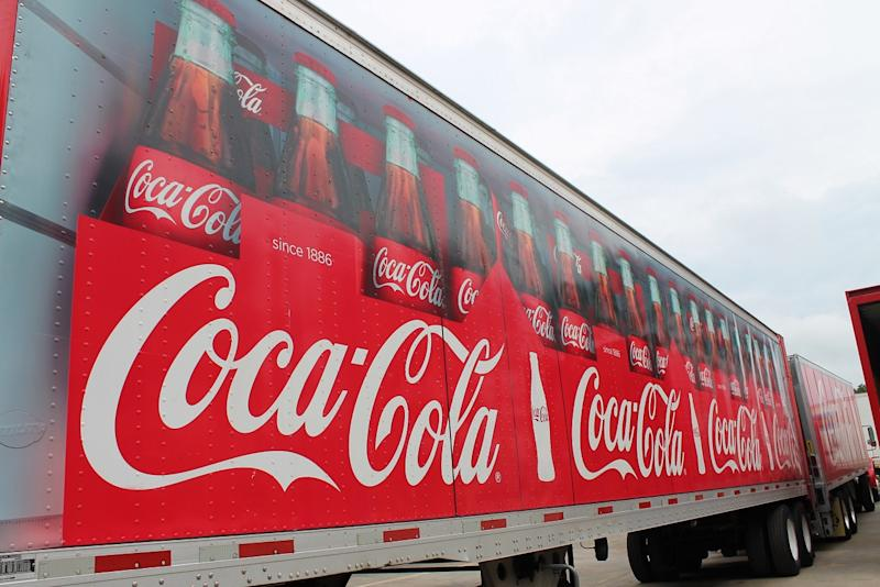 Side of semi trailer truck with Coca-Cola bottles on it.