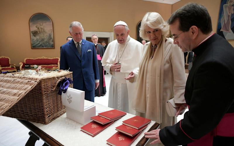 Pope Francis exchanges gifts with Britain's Prince Charles and his wife Camilla, Duchess of Cornwall, during a private audience at the Vatican - Credit: REUTERS
