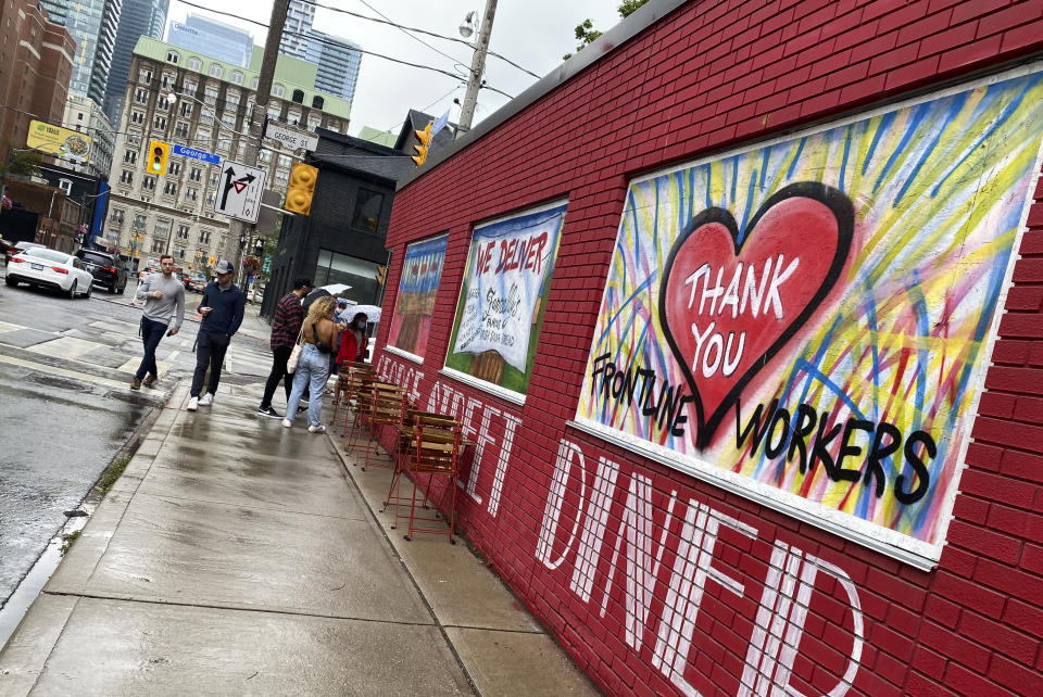 People line up to dine at a restaurant that has painted its walls to support the frontline workers in downtown Toronto, Canada, on Saturday, July 17, 2021. With nearly 70% of its adult population receiving at least one dose of a COVID-19 vaccine, Canada has the world's highest vaccination rate and is now moving on to immunize children, who are at far lower risk of coronavirus complications and death. (AP Photo/Kamran Jebreili)