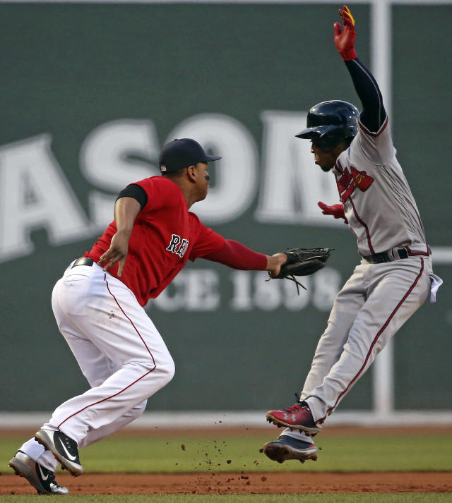 Boston Red Sox third baseman Rafael Devers, left, forces out Atlanta Braves' Ozzie Albies on a ground ball by Kurt Suzuki in the first inning of an interleague baseball game at Fenway Park, Friday, May 25, 2018, in Boston. (AP Photo/Elise Amendola)