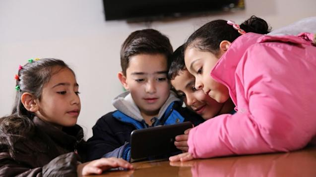 Children playing educational game on smartphone