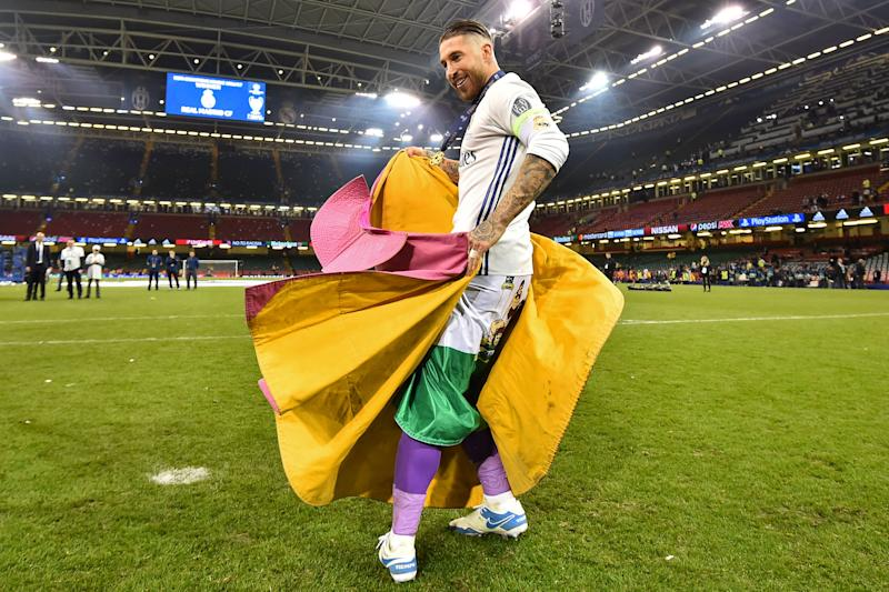 Real Madrid captain Sergio Ramos celebrates with a bullfighter's cape after Real Madrid won the UEFA Champions League final football match between Juventus and Real Madrid at The Principality Stadium in Cardiff, south Wales, on June 3, 2017. / AFP PHOTO / Glyn KIRK (Photo credit should read GLYN KIRK/AFP/Getty Images)