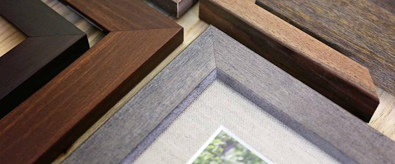 A collection of solid wood photo picture frame corner samples are displayed on a table.