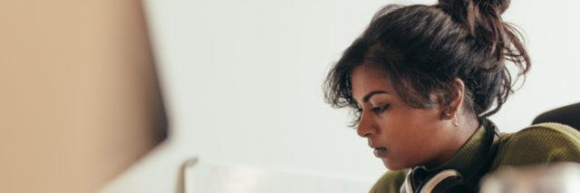 A photo of a South Asian woman sitting at her desk.