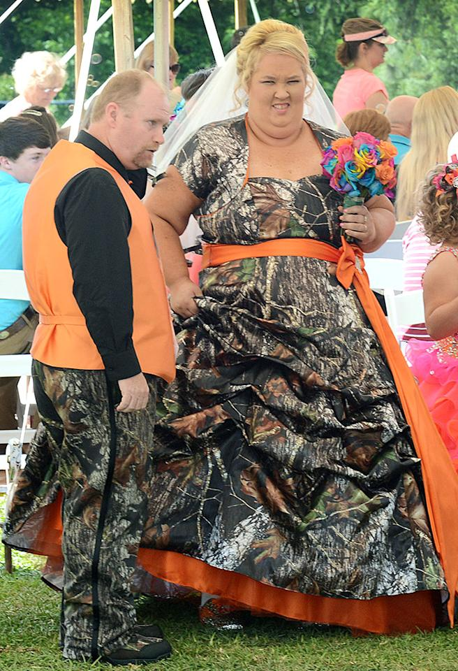 June 'Mama June' Shannon married Mike 'Sugar Bear' Thompson in Gerogia. The reality show mom ditched the traditional white gown for a more colorful ensemble in a cap-sleeve camouflage gown with orange trim and ribbons for her walk down the aisle. The blushing bride even carried a bouquet of multi-colored roses as she made her way down the aisle. 