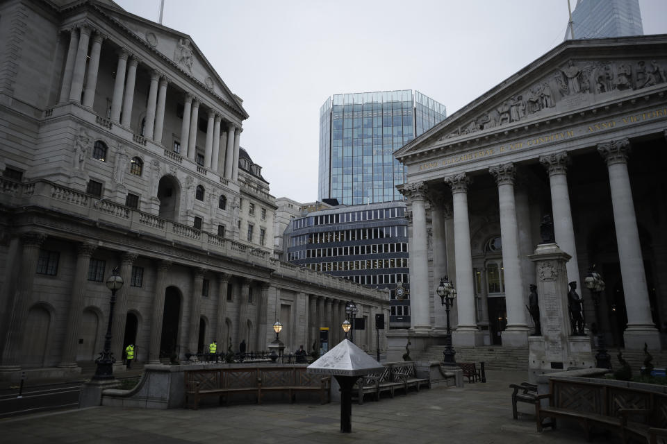 Security guards stand outside the Bank of England, left, next to the Royal Exchange, right, in the City of London financial district. Photo: Matt Dunham/AP