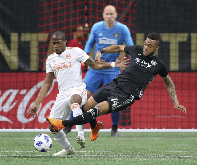 Atlanta United midfielder Darlington Nagbe, left, works against Sporting Kansas City forward Kiry Shelton, right, with goalkeeper Brad Guzan watching during the first half of an MLS soccer match Wednesday, May 9, 2018, in Atlanta. (Curtis Compton/Atlanta Journal-Constitution via AP)
