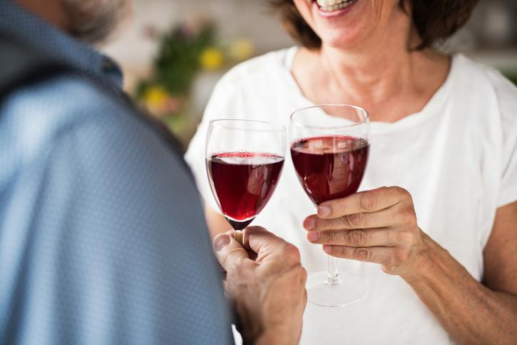 A senior couple in clinking glasses with red wine is pictured.