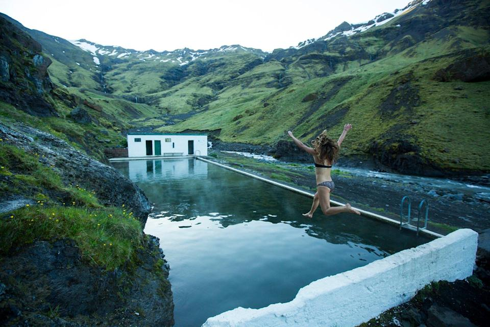 A woman jumping into a hot spring in Iceland.