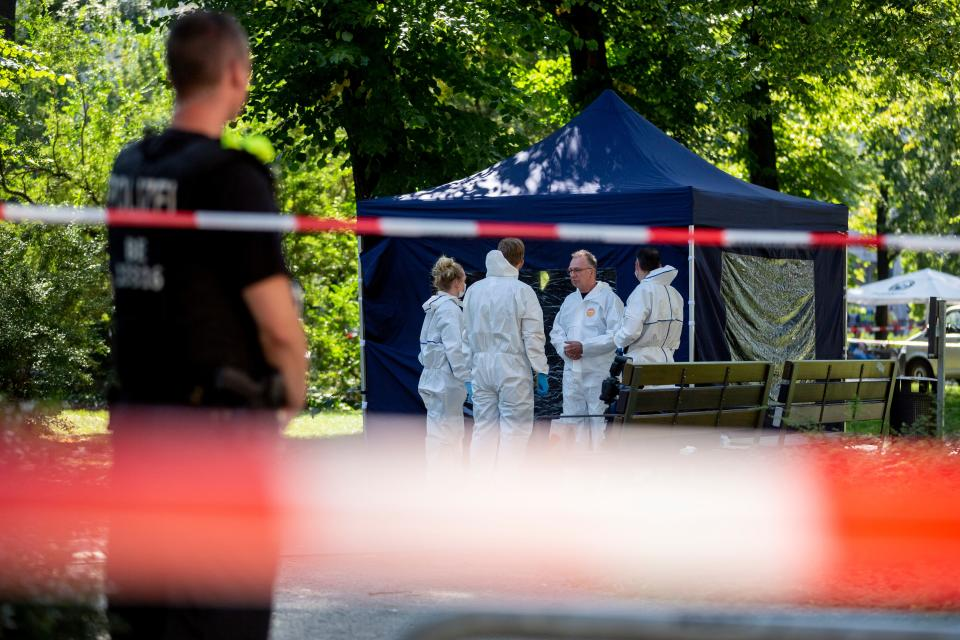 """Picture taken on August 23, 2019 shows forensic experts of the police securing evidences at the site of a crime scene in Berlin's Moabit district, where a man of Georgian origin was shot dead. - German police were investigating on August 25, 2019 the assassination-style killing in a Berlin park of the Georgian man who was reportedly a former special forces commando and Chechnya war veteran. Police have arrested a 49-year-old suspect from Russia's Chechnya republic over the murder of the man media identified as Zelimkhan Khangoshvili. The killer had approached his victim from behind, as he was on his way to a mosque, shot him and fled by bicycle in what one witness described as an """"execution"""" style killing. (Photo by Christoph Soeder / dpa / AFP) / Germany OUT        (Photo credit should read CHRISTOPH SOEDER/DPA/AFP via Getty Images)"""