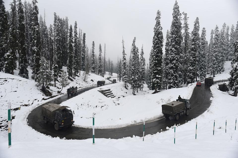 SRINAGAR, INDIA - NOVEMBER 16: Army vehicles make their way past a snow lined bend on Gulmarg road after the seasons first snowfall in the region on November 16, 2020 in Srinagar, India. (Photo by Waseem Andrabi/Hindustan Times via Getty Images)