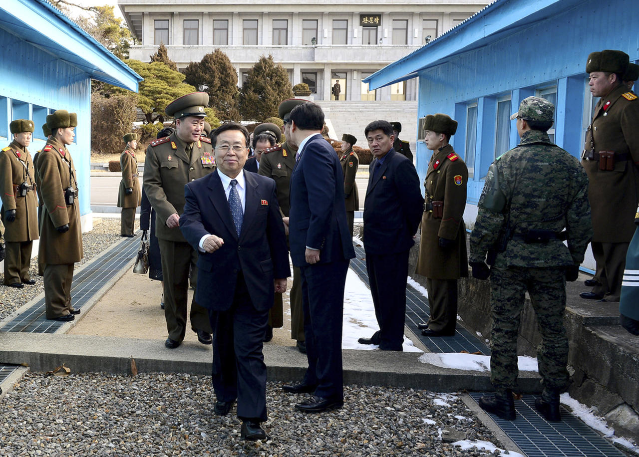 In this photo released by the South Korean Unification Ministry, North Korean chief delegate Won Tong Yon, center left, walks with other delegates after crossing a military demarcation line, which has separated the two Koreas since the Korean War, for a meeting with South Korean delegates at the border village of Panmunjom, South Korea, Friday, Feb. 14, 2014. The rival Koreas sat down Friday for a second round of talks this week at a border village as the North's calls for a delay of annual South Korea-U.S. military drills threaten plans for the resumption of emotional reunions of war-divided families. (AP Photo/South Korean Unification Ministry)