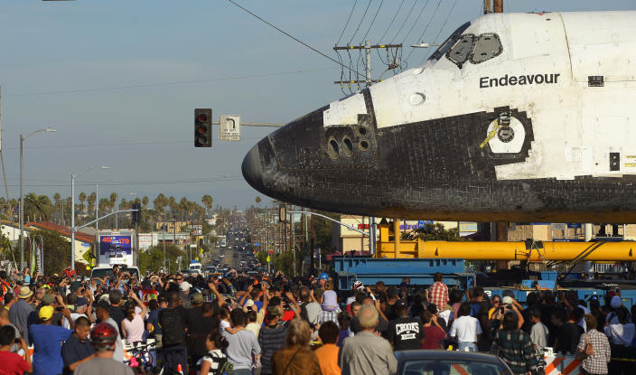 The space shuttle Endeavour is slowly moved down Crenshaw Blvd. at Slauson Ave., Saturday, Oct.13, 2012, in Los Angeles. The shuttle is on its last mission — a 12-mile creep through city streets. It will move past an eclectic mix of strip malls, mom-and-pop shops, tidy lawns and faded apartment buildings. Its final destination: California Science Center in South Los Angeles where it will be put on display. (AP Photo/Mark J. Terrill)