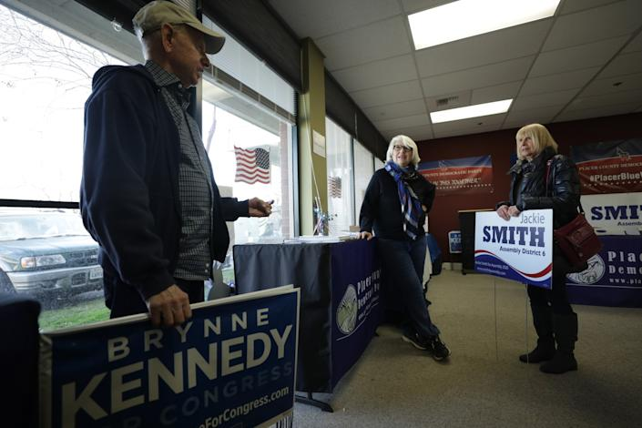 Rosemary Dukelow, center, speaks with Chuck and Audrey Ehrlich, who picked up lawn signs for Democratic candidates.