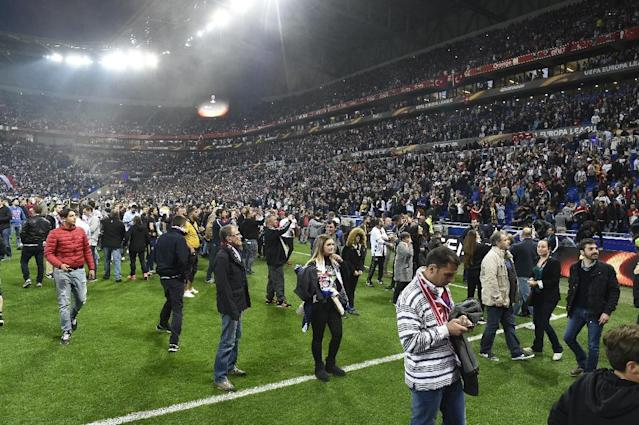 People stand on the pitch as Besiktas and Lyon fans fight before their UEFA Europa League first leg quarter final match on April 13, 2017, at the Parc Olympique Lyonnais stadium in Decines-Charpieu, central-eastern France (AFP Photo/PHILIPPE DESMAZES)